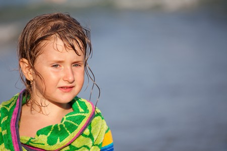 wrapped up: Little girl wrapped up in a towel at the beach.