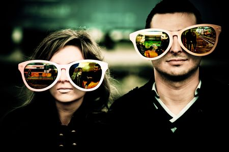 Young couple wearing large glasses which reflect the beginning of their relationship.
