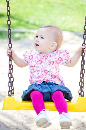 babyhood: Small baby girl spending time outdoor on a warm autumn day. Stock Photo