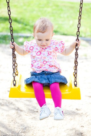 Small baby girl spending time outdoor on a warm autumn day. photo