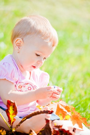baby girl playing: Small baby girl spending time outdoor on a warm autumn day. Stock Photo