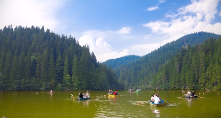tourist destinations: BICAZ, ROMANIA - AUGUST 17: Tourists with boats on the Red Lake on August 17, 2010 in Bicaz, Romania. The Red Lake and Bicaz Gorges are one of the busiest tourist destinations in Romania.