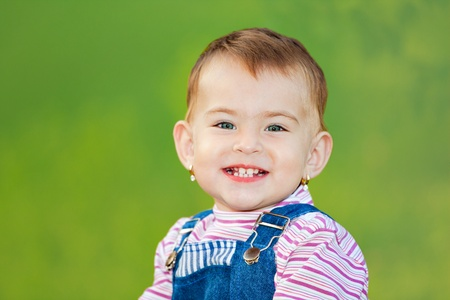 Portrait of a one year old baby girl outdoor smiling and showing her teeth. photo