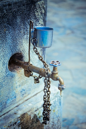 Vertical view of a old water tap with a metal cup.