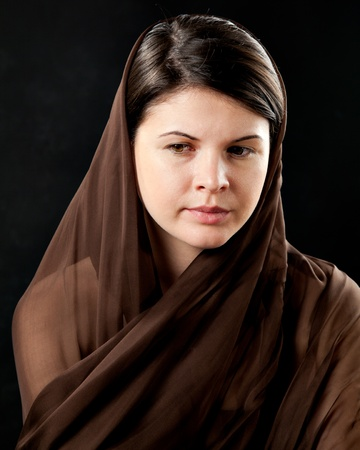 20 year old: 20 year old woman wearing a scarf, looking sad, against a black background. Stock Photo