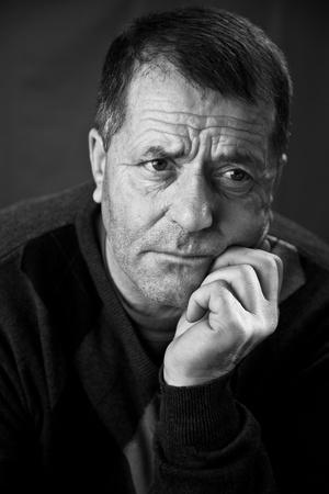 Black And White Portrait of a Middle aged Mann mit einen ernsten Blick auf seinem Gesicht. Lizenzfreie Bilder