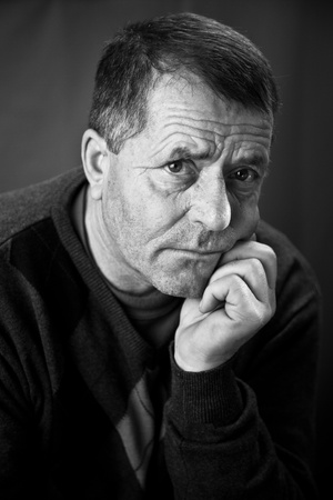 Fine art portrait of a mature man looking at the camera with a serious look on his face.