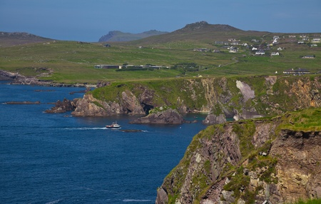 dunquin: Landscape of coast of Dingle and ferry enterring Dunquin harbour and bay, Dingle Peninsula, Ireland. Stock Photo