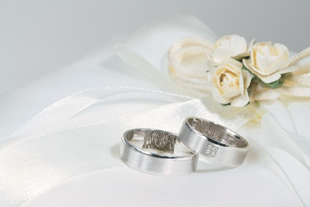 Wedding rings on a white sating ring bearer pillow with flowers.