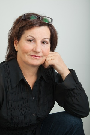 portrait of a woman: Middle aged business woman dressed in black on grey background.