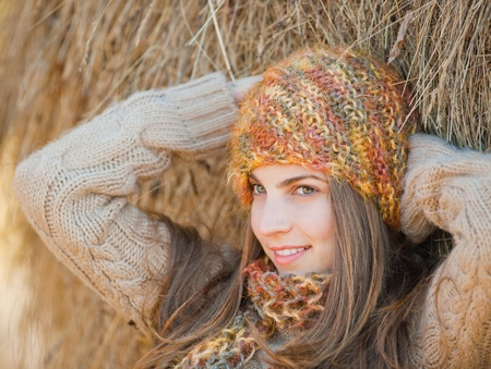Beautiful young woman relaxing under a hay stack in autumn. Stock Photo - 11102987