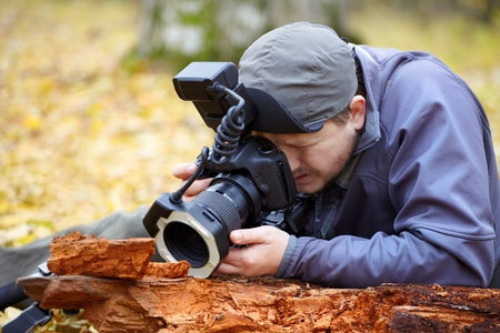Biologist photographing small details with professional equipment in the forest in autumn. photo