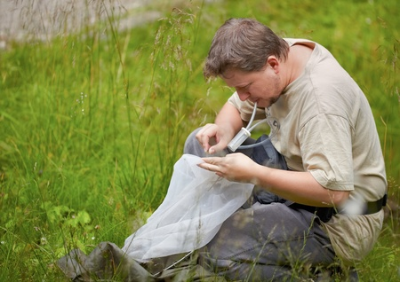 Entomologist collecting bugs from the net with an entomological aspirator in summer.