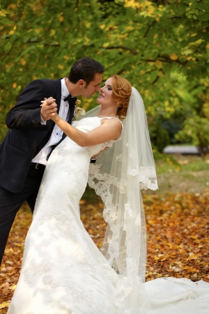 Bride and groom portrait outdoor in autumn.