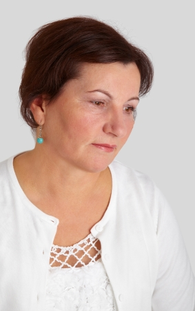 fifty: Portrait of a beautiful middle aged woman against a grey background.