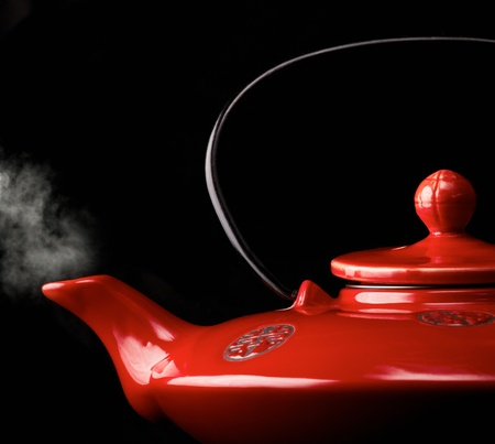 Red chinese teapot with steam isolated on black. Stock Photo