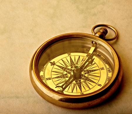 Antique golden compass on old paper, studio shot.