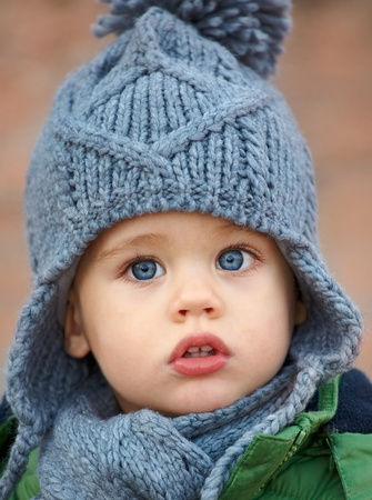 Portrait of a little baby boy wearing a cute hat in autumn.