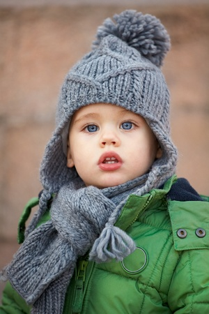 Portrait of a little baby boy wearing a cute hat in autumn.