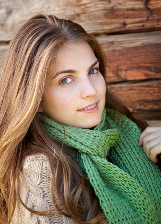 Portrait of a beautiful young woman outdoor on a chilly day against a wooden wall. photo