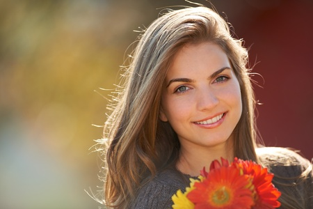 Portrait of a young girl holding red flowers outdoors.