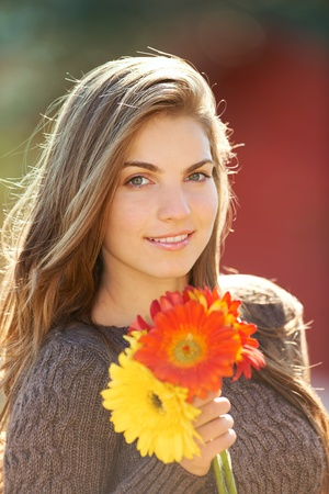 Portrait of a young woman outdoor in autumn holding beautiful flowers.