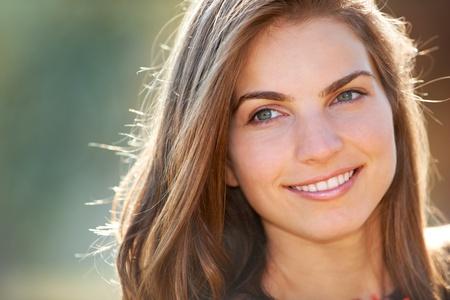 20: Retrato de una joven sonriendo mientras al aire libre bajo el sol.