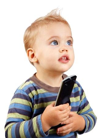 Studio Portrait eines glücklichen 1 Jahr altes Baby Jungen, die eine TV-Fernbedienung und blickte auf.
