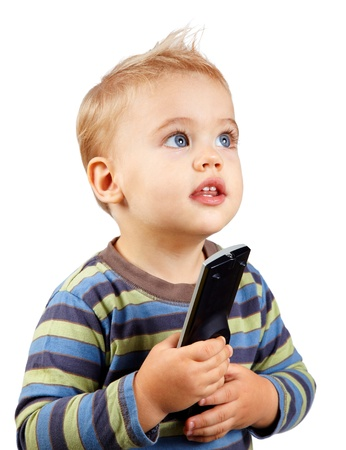 Studio portrait of a happy one year old baby boy holding a tv remote and looking up.