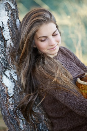 20 year old girl: Portrait of young woman leaning against a tree in autumn. Stock Photo