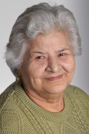 Portrait of a beautiful grandmother, smiling at camera, studio shot. photo