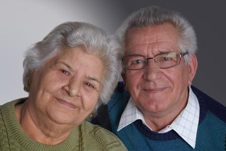 Elederly couple portrait smiling, studio shot, looking at camera.