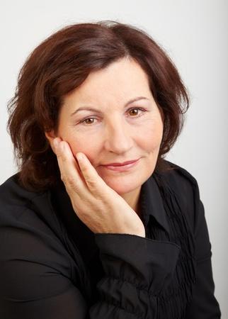 Porträt einer schönen Frau mittleren Alters vor einem grauen Hintergrund.