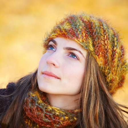 Closeup portrait of a beautiful young woman looking up towards the sky in autumn. Stock Photo