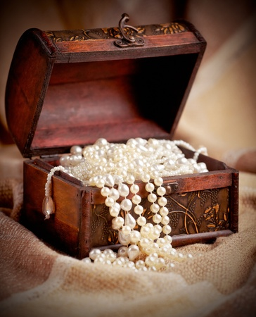Still life with wooden treasure chest with pearl necklaces. photo