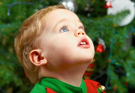 Cute 1 year old baby boy at the Chriistmas tree.