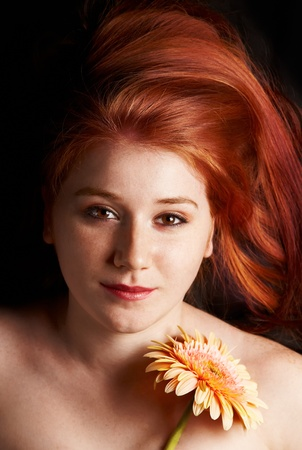 suave: Low key portrait of a young redhead woman with bare shoulders lying down on with a flower.