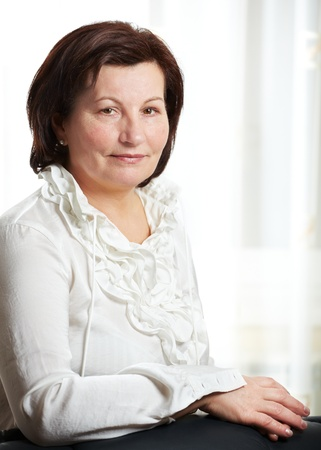 50: 50 year old beautiful business woman portrait at the office.  Stock Photo