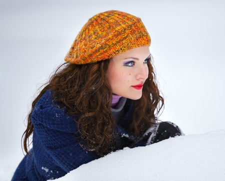 20 year old: Portrait of a beautiful 20 year old woman outdoor in winter sitting behind a pile of snow.