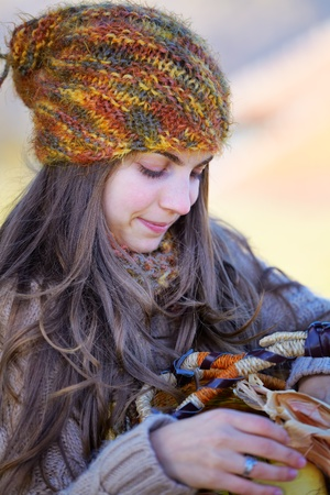 Young woman outdoor with a basket of fruits in autumn. photo