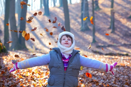 Beautiful 7 year old little girl throwing leaves in the woods. photo