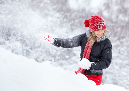 Woman being hit by a snow ball in wintertime. Stock Photo