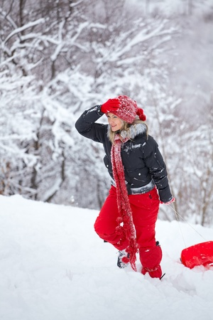Young woman having fun in the snow, pulling a slay on the slope. photo