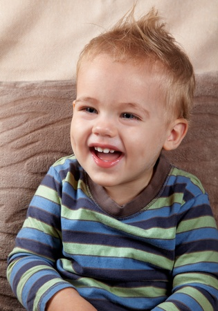 indoor shot: Portrait of a little baby boy laughing outloud. Indoor shot. Stock Photo