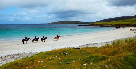 horse riding: Four riders and horses on the Sellerna beach, Cleggan, in summertime, Ireland.