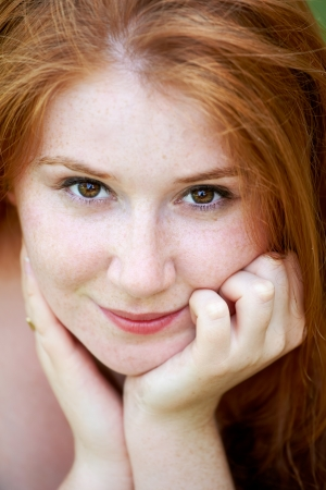 20 year old: Portrait of a beautiful 20 year old redhead woman looking at camera and smiling. Stock Photo