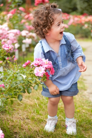 Portrait of happy two year old little girl outdoor in a rose garden. photo