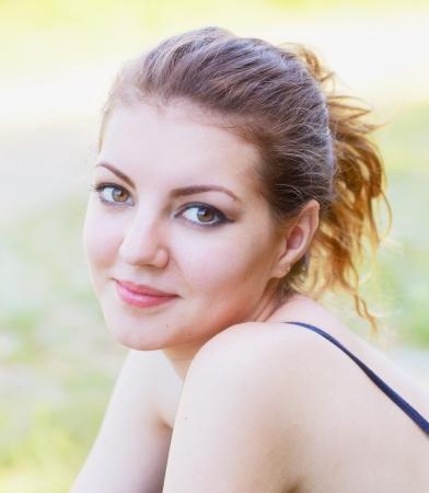 Porträt einer schönen 20-jährige Frau genießen einen Sommertag im Freien.