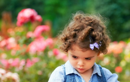 pouty: Portrait of sad two year old little girl outdoor in a rose garden.