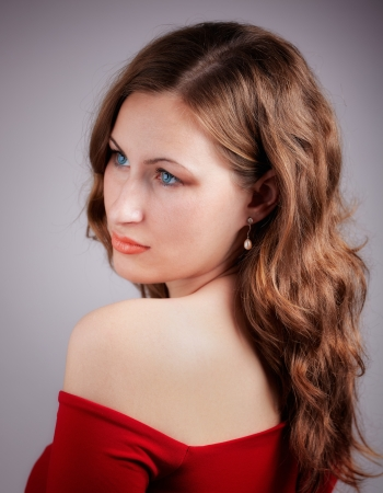 20 year old: Studio portrait of a beautiful 20 year old redhead woman with red dress.